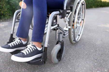 Young woman in wheelchair outdoors, closeup