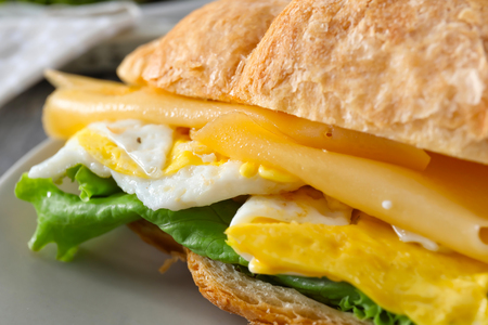 Tasty croissant sandwich with fried egg on plate, closeup