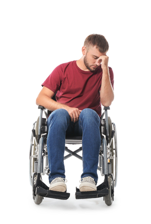 Depressed young man in wheelchair on white background Imagens