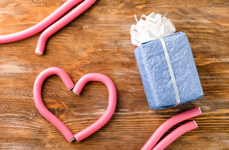 Heart made of hair curlers and gift box on wooden background