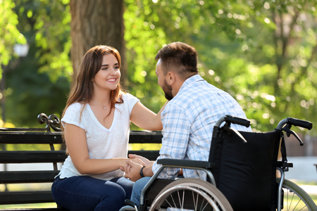 Young man in wheelchair with his wife outdoors Imagens