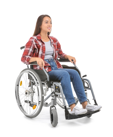 Young woman sitting in wheelchair on white background