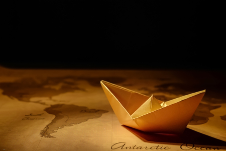 Origami boat on vintage world map. Travel concept