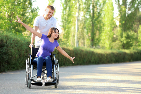 Happy young woman in wheelchair and her husband outdoors Banque d'images - 119212933