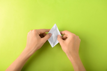 Woman making origami boat on color background