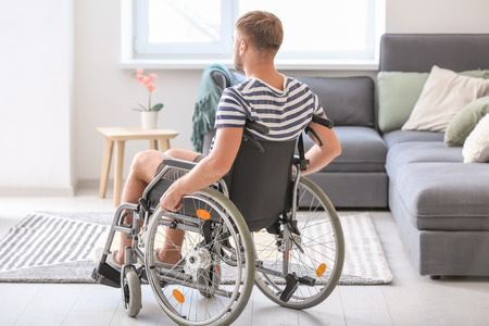 Young man in wheelchair at home Imagens