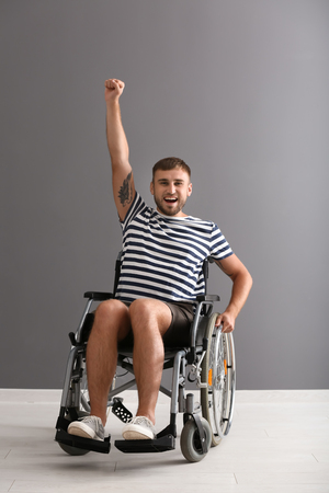 Happy young man in wheelchair against grey wall