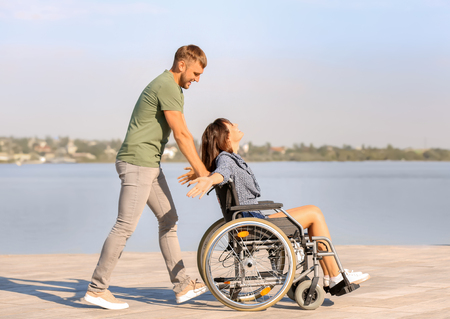 Happy young woman in wheelchair and her husband near river