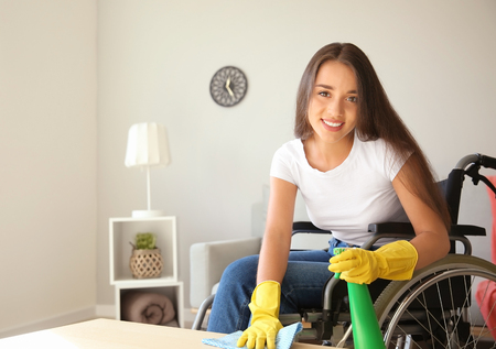 Young woman in wheelchair cleaning table at home