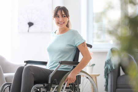 Happy young woman in wheelchair at home