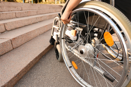 Young woman in wheelchair near stairs outdoors