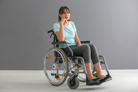 Young woman in wheelchair against grey wall