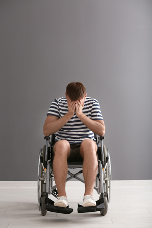 Depressed young man in wheelchair against grey wall Imagens