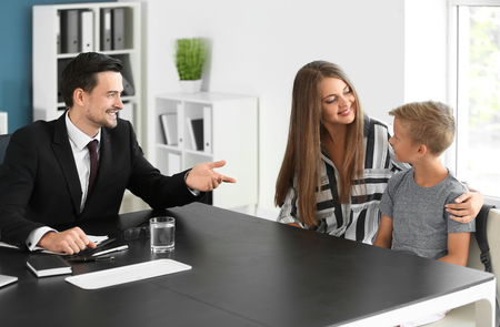 Young woman and her son meeting with headmaster at school Stockfoto