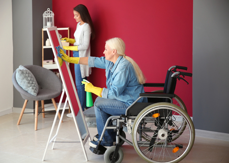 Mature woman in wheelchair and her daughter cleaning home