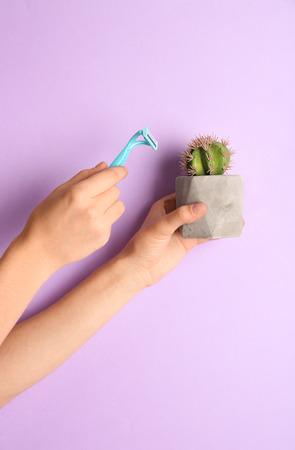 Woman holding razor and cactus on color background 版權商用圖片