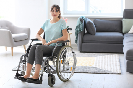 Young woman in wheelchair at home Imagens