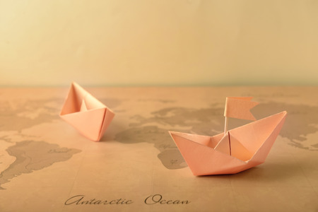 Origami boats on vintage world map. Travel concept Stockfoto