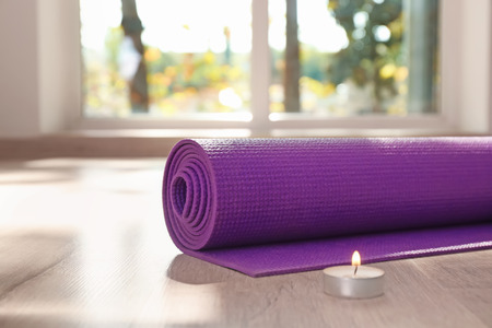 Yoga mat and burning candle on floor