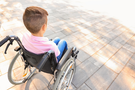 Boy in wheelchair outdoors Imagens