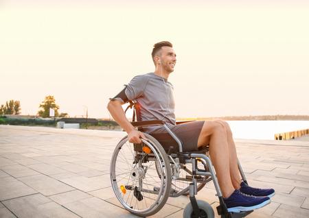 Jonge man in rolstoel die buiten naar muziek luistert Stockfoto