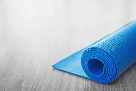 Rolled yoga mat on wooden floor