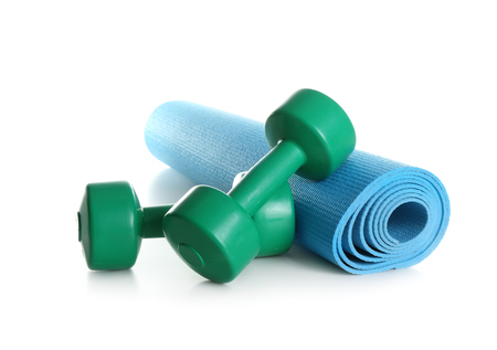 Yoga mat with dumbbells on white background