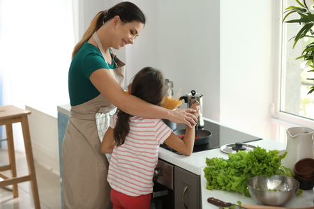 Mother and daughter cooking together in kitchen Stockfoto