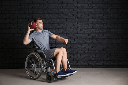 Young man with rugby ball sitting in wheelchair against dark brick wall Stock Photo