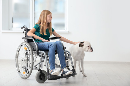Teenage girl in wheelchair and her dog at home