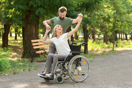 Beautiful woman in wheelchair with man dancing outdoors Imagens