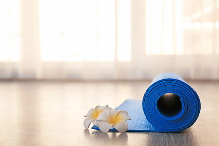 Rolled yoga mat and flowers on floor