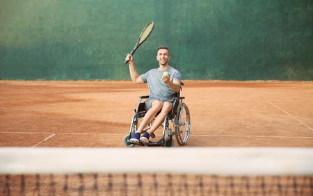 Young man in wheelchair playing tennis on court