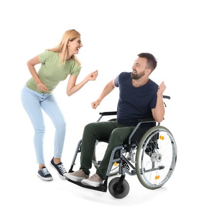 Man in wheelchair with beautiful woman dancing on white background Imagens