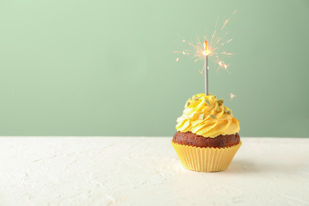 Delicious birthday cupcake with sparkler on white table