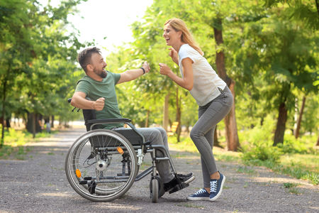 Man in wheelchair with beautiful woman dancing outdoors