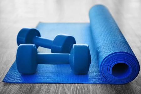 Yoga mat with dumbbells on wooden floor