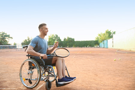 Young man in wheelchair playing tennis on court Banque d'images - 119753084