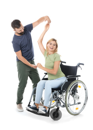 Beautiful woman in wheelchair with man dancing on white background