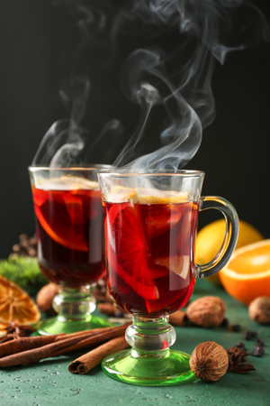 Glass cups of delicious hot mulled wine on color table Stockfoto
