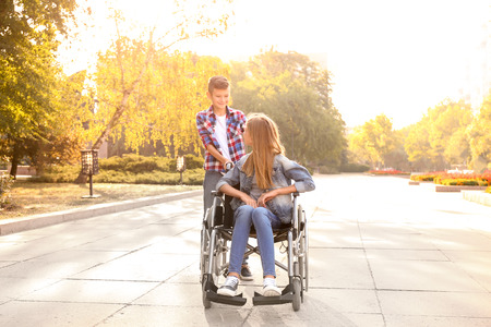 Teenage girl in wheelchair and her brother outdoors Standard-Bild - 119754077
