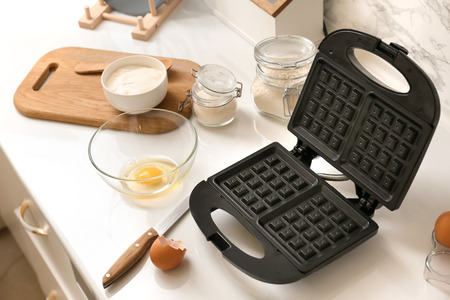 Waffle iron and ingredients for cooking on kitchen table