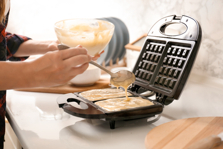 Woman preparing homemade waffles in kitchen