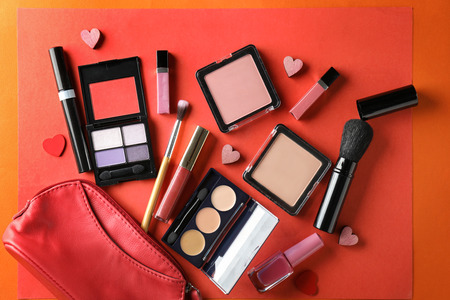 Set of cosmetics with small hearts and bag on color background