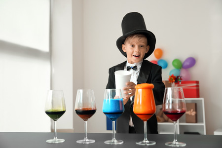Cute little magician showing trick indoors Standard-Bild - 119755222