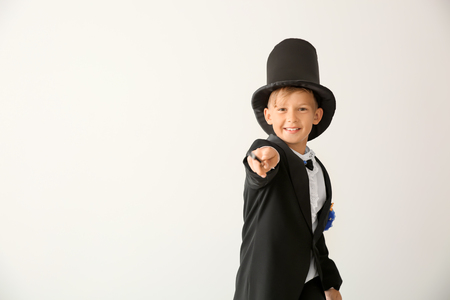 Cute little magician showing tricks on white background