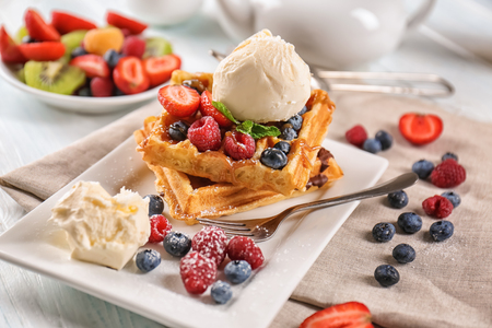 Delicious waffles with berries and ice cream on plate