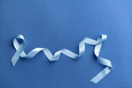 Blue ribbon on color background. Cancer concept