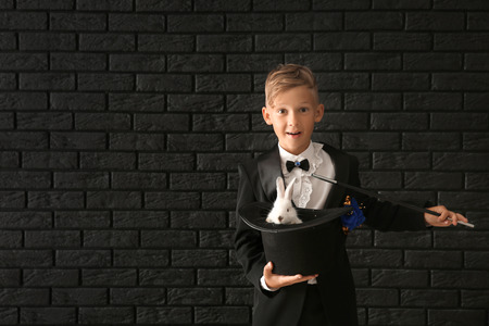 Cute little magician holding hat with rabbit against dark brick wall