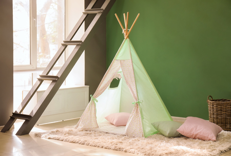 Cozy play tent for kids near color wall 版權商用圖片